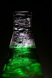 Isolated. Green liquid bubbling in a glass beaker on a black background stock images