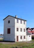 Isolated abandoned three storage building near new houses Royalty Free Stock Image