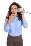 Isolated amazed funny business woman calling with tin can phone. Isolated amazed funny business woman calling with tin can phone wearing blue blouse Stock Photo