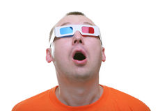 Isolated amazed young man with 3d anaglyph glasses. Holding his hands up on his face stock photography