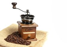 Vintage manual coffee grinder with coffee beans on wooden spoon. Isolated antique coffee grinder and coffee beans Royalty Free Stock Photos