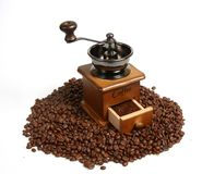 Vintage manual coffee grinder with coffee beans on wooden spoon. Isolated antique coffee grinder and coffee beans on wooden spoon Royalty Free Stock Image