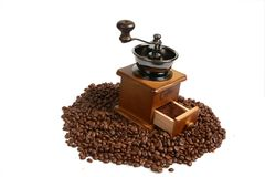 Vintage manual coffee grinder with coffee beans on wooden spoon. Isolated antique coffee grinder and coffee beans on wooden spoon Royalty Free Stock Images