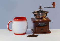 Isolated antique kitchen grinder witch cup of caffe. And caffe Royalty Free Stock Images