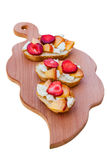 Isolated appetizer on a cutting board. Bruschetta with peach, strawberry and adygei cheese on a board Stock Images