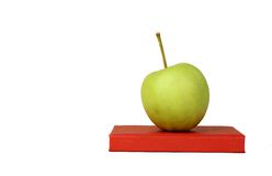 Isolated apple and book. Isolated green apple on top of book; education or back to school concept royalty free stock photography