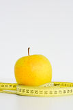 Isolated apple and measuring tape suggesting diet concept Stock Image