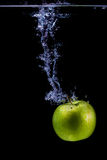 Isolated apple splashing Royalty Free Stock Images