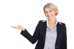 Isolated attractive mature businesswoman is presenting on white. Royalty Free Stock Photos