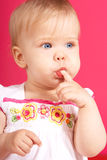 Isolated babygirl. Beautiful babygirl sucking a finger on pink background Royalty Free Stock Image