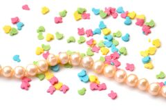 Isolated background of bright confectionery topping in form of animals and string of beads of sea pink pearls on white stock photo
