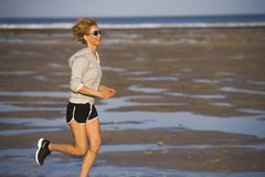 Isolated background portrait of young happy and attractive fit woman running on the beach in outdoors jogging workout in fitness t stock image