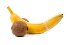 Isolated banana with condom. And kiwi Stock Photo