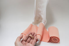Isolated bandage clip in woman hand with leg splint Stock Image