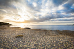 Isolated beach at sunrise with clouds, Sardinia, Italy Royalty Free Stock Photos