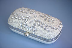 Isolated beads and rhinestone embellished clutch, on a blue suede leather cloth. Accessories, concepts, details, ideas and themes, bride morning preparation Royalty Free Stock Images