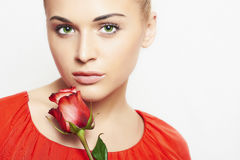 Isolated beautiful woman with flowers. girl and flower. beautiful blond girl in red dress. close-up portrait. Red rose Stock Photo