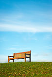 Isolated bench against blue sky. Lone bench in park on bright sunny Autumn day Royalty Free Stock Photo
