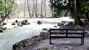 A isolated bench in English garden front a river, Munich Germany. Isolated bench in English garden front a river, Munich Germany stock footage