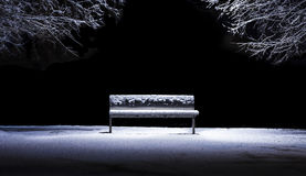 Isolated bench in a park after a snowfall Stock Photo