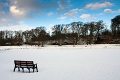 Isolated bench with snow Royalty Free Stock Images