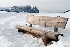 Isolated bench in snow scape. Isolated wooden bench on snow scape in dolomiti, Alps Royalty Free Stock Photo