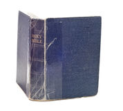 Isolated Bible. An old blue bible is being held together with tape and isolated against a white background Royalty Free Stock Image