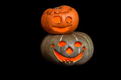 Two stacked Halloween pumpkins with smiley faces on black background Royalty Free Stock Images