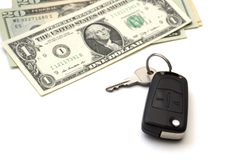Isolated black car key and a bunch of banknotes of American dollars stock photography