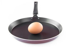 Isolated black frying pan with uncooked egg Stock Photo