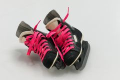 Isolated black old-fashion hockey skates with pink bootlace. Hockey boots are on ice Royalty Free Stock Photo
