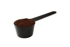 Isolated black plastic ground coffee scoop. Isolated black plastic scoop of fresh ground coffee Stock Photo