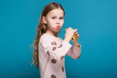Pretty, little girl in sweater with brunet hair hold a burger. Isolated on blue, attractive caucasian brunette child with long hair, in beige coat and blue jeans Royalty Free Stock Photos