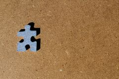 Blue cardboard puzzle piece on brown wooden background. Isolated blue cardboard puzzle piece on brown wooden background royalty free stock image