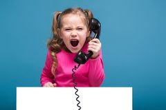 Attractive little cute girl in pink shirt with monkey and blue trousers hold empty poster and talks a phone. Isolated on blue, cute little caucasian brunette Royalty Free Stock Photos
