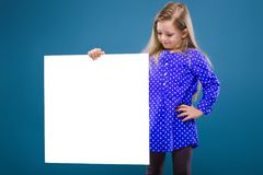 Cute little girl in purple dress holds empty poster Royalty Free Stock Photos