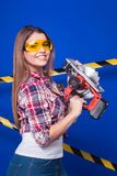 Pretty sexy worker girl in chechered shirt, build goggles and je. Isolated on blue, smiling sexy brunette caucasian worker girl in chechered shirt, yellow build Royalty Free Stock Photos