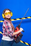 Pretty sexy worker girl in chechered shirt, build goggles and je. Isolated on blue, smiling sexy brunette caucasian worker girl in chechered shirt, yellow build Stock Images