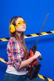 Pretty sexy worker girl in chechered shirt, build goggles and je. Isolated on blue, smiling sexy brunette caucasian worker girl in chechered shirt, yellow build Royalty Free Stock Photography