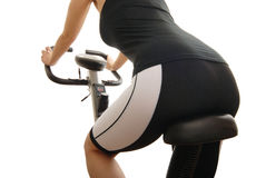 Isolated body of young woman on a spinning bicycle. Isolated body of young woman riding on a spinning bicycle from back Royalty Free Stock Images