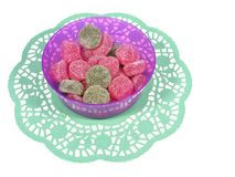 Isolated bowl with many sugar candies. Red and green sugar sweeties in a plastic  bowl on a green paper lace over white Royalty Free Stock Photography