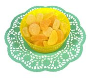 Isolated bowl with many sugar candies. Yellow sugar sweeties in a plastic  bowl on a green paper lace over white Stock Photography