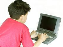 Isolated boy. Typing on a laptop Stock Photography