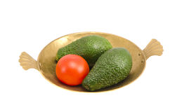 Isolated brass plate with avocado and tomato Stock Photo