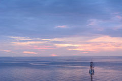 Isolated broadcast tower on the beach. Isolated broadcast tower on the beach in beautiful sunrise scenario Royalty Free Stock Image