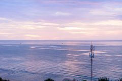Isolated broadcast tower on the beach. Isolated broadcast tower on the beach in beautiful sunrise scenario Royalty Free Stock Photos