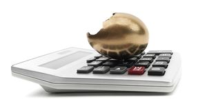 Cracked Golden Egg On A Calculator. Isolated broken gold egg on a calculator Stock Images