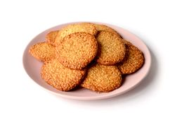 Isolated bunch of round biscuits with sesame on a light pink pla royalty free stock image