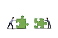 Isolated business partner putting together two puzzle. Business partner putting together two puzzle pieces - isolated on white background Royalty Free Stock Photo
