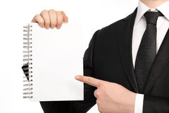 Isolated businessman holding a notebook or piece of paper Royalty Free Stock Photography